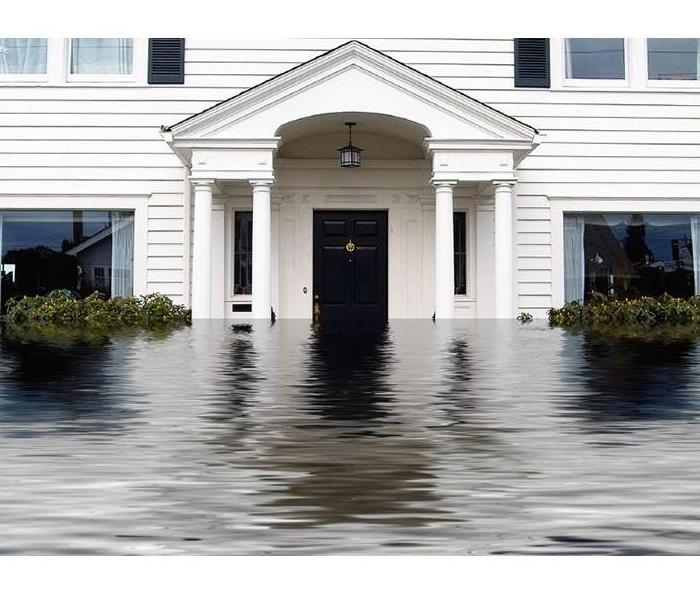Front of two story white house with water covering half of the front door and windows.